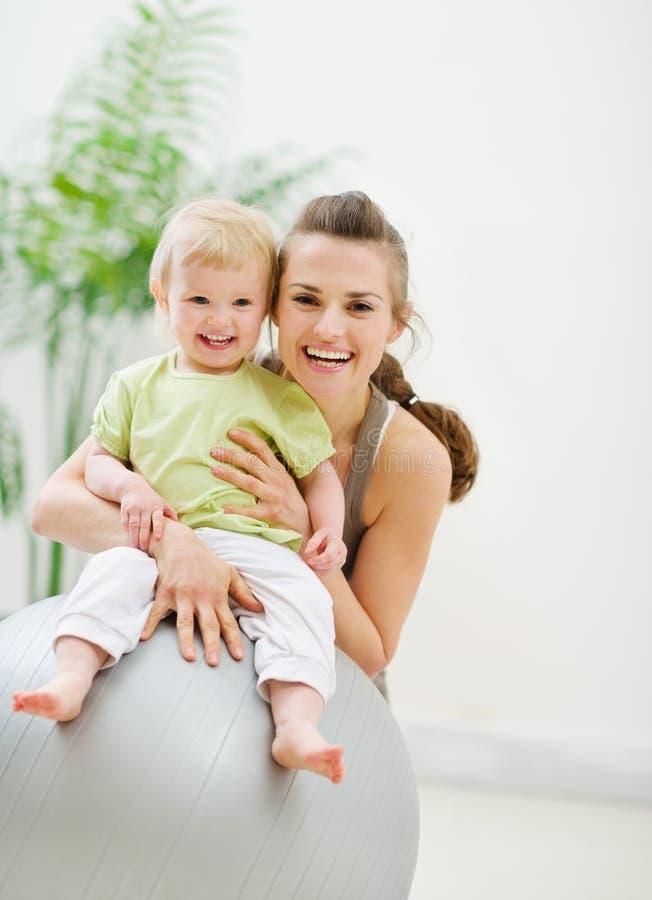 Portrait der glücklichen Mutter und des Schätzchens in der Gymnastik lizenzfreies stockbild
