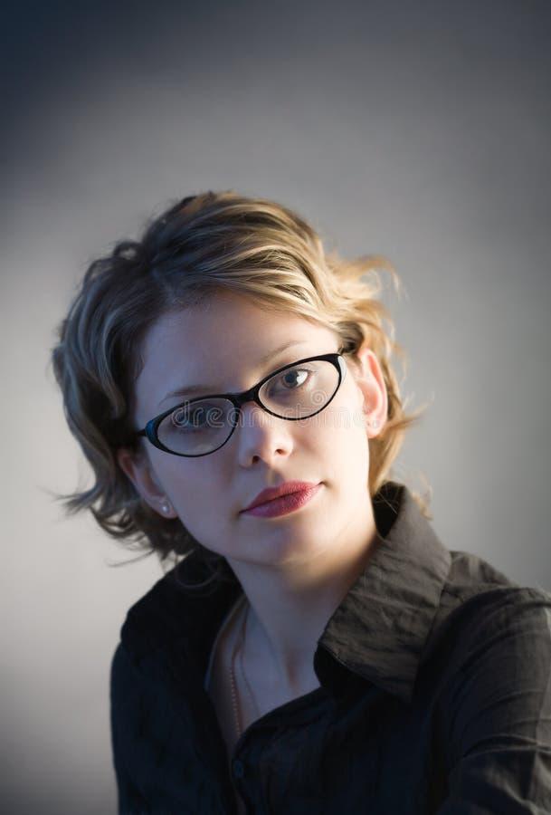Portrait der hübschen Frau in den Gläsern über Schwarzem lizenzfreie stockbilder