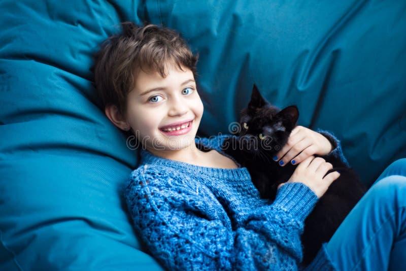 Portrait der 7-jährigen lächelnden Mädchen mit kurzen Haarschnitt auf klassisch blauen Stuhl in klassisch blauen Pullover mit ihr stockbilder