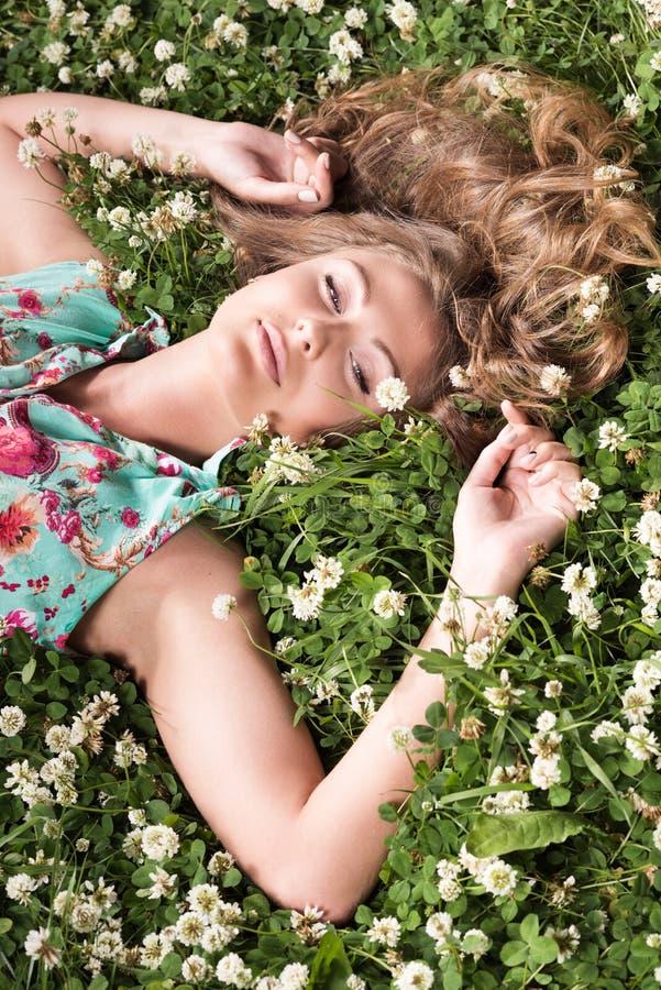 Portrait der jungen Frau liegend auf dem Gras lizenzfreie stockfotos