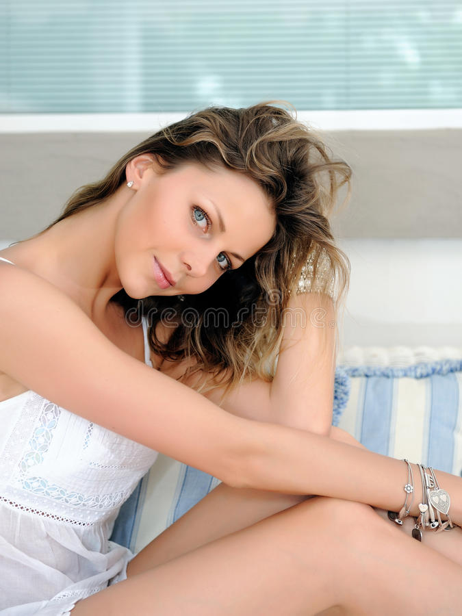 Portrait der jungen hübschen Frau, die auf einem Sofa sich entspannt lizenzfreies stockfoto