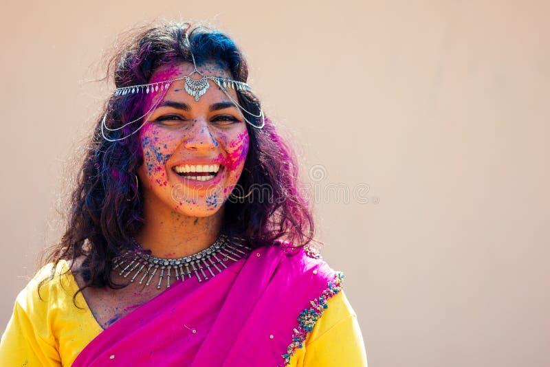 Portrait der jungen indischen Gesicht in Farbe Woman in traditionell indianischem rosa Outfit mit Juwelier feiern Holi Farbe stockbild
