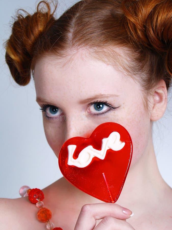 Portrait der jungen redheaded Frau mit Lutscher stockbilder