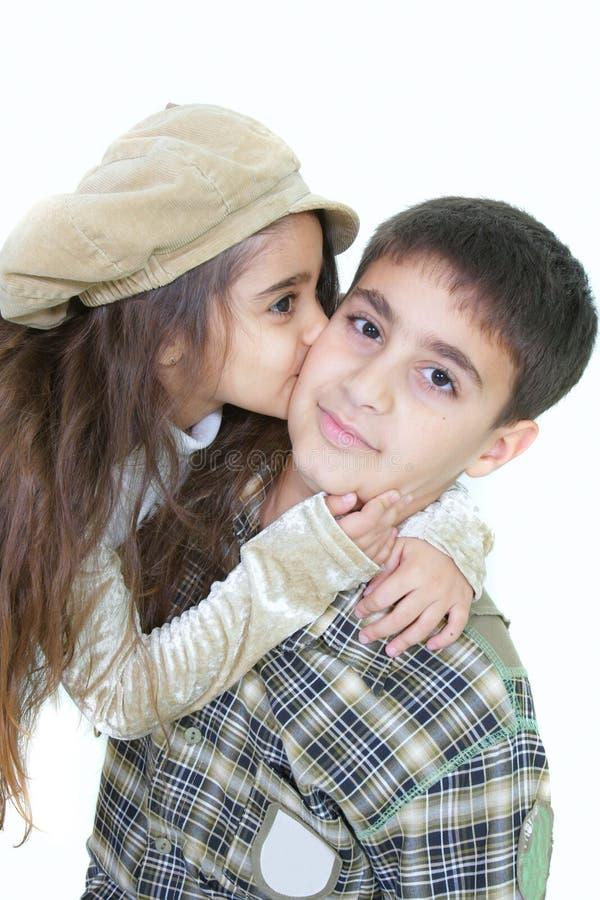 Portrait der jungen Schwester älteren Bruder küssend lizenzfreie stockfotografie