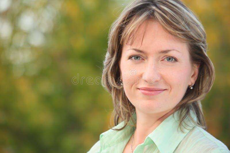 Portrait der lächelnden Frau im frühen Fallpark stockfotografie