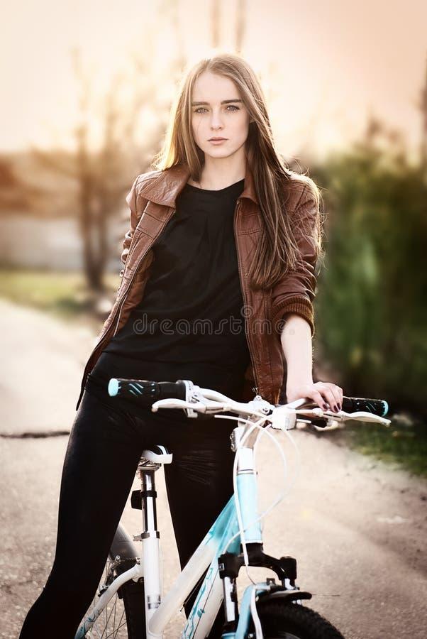 Portrait der recht jungen Frau mit Fahrrad in einem P stockfoto