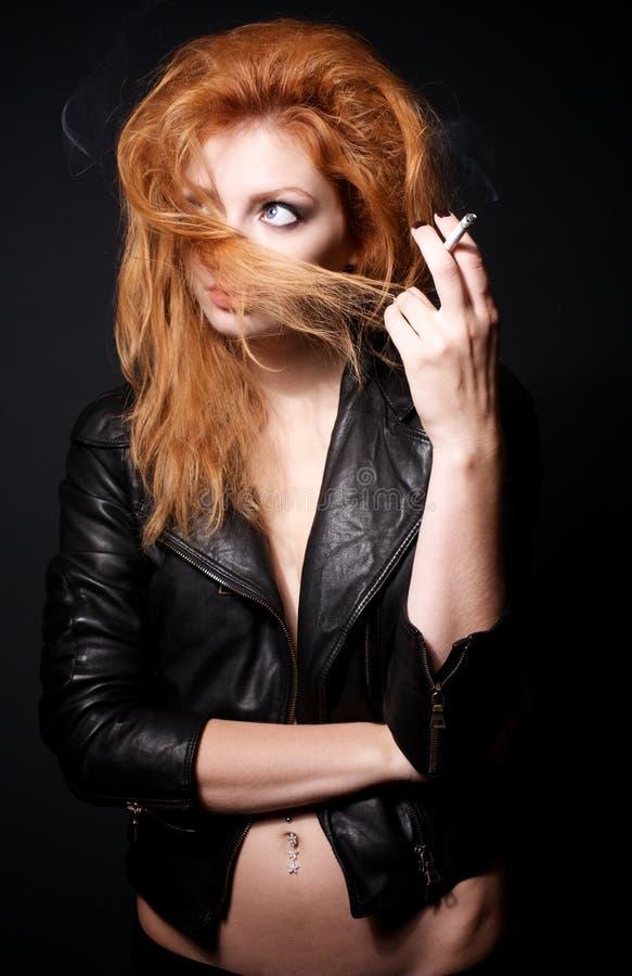 Portrait der Redheadfrau mit einer Zigarette lizenzfreie stockfotografie