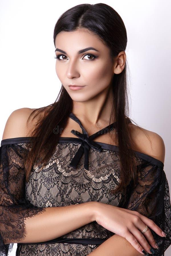Portrait der schönen Brunettefrau im schwarzen Kleid Modefotoschuß lizenzfreie stockfotos