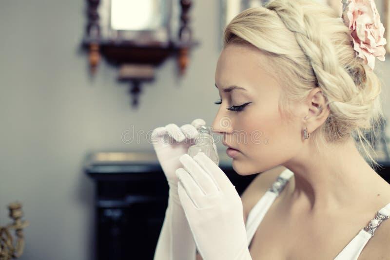 Portrait der schönen Frau einen Duftstoff riechend lizenzfreies stockbild