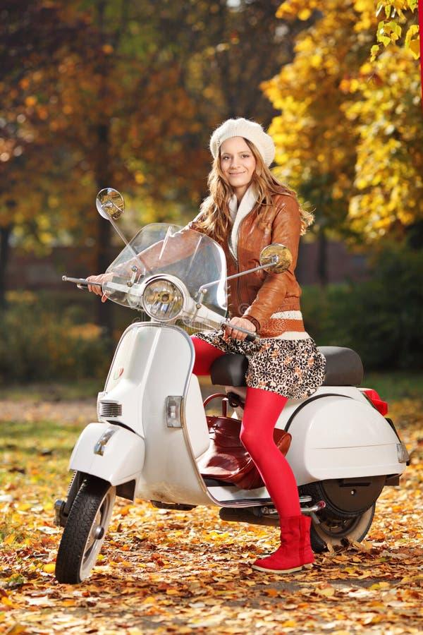 Portrait der schönen jungen Frau auf Roller stockbild