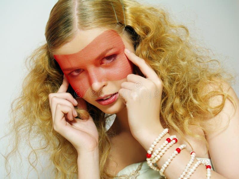 Portrait der schönen jungen Frau, die rote Schablone trägt stockfotografie