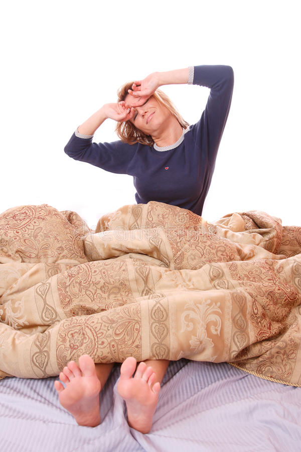 Portrait der schönen lächelnden Frau auf Bett lizenzfreie stockbilder