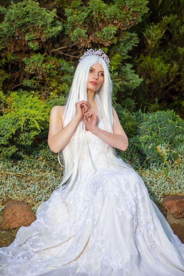 Portrait der sensual entspannten kaukasischen Braut mit Tiara und langer weißer Haarbugel im Grünen Garten im Freien lizenzfreie stockfotografie