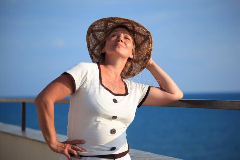 Portrait der von mittlerem Alter Frau im Hut auf Balkon lizenzfreie stockbilder