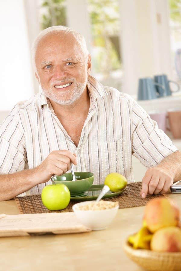 Portrait des älteren Mannes, der Morgentee trinkt stockbild