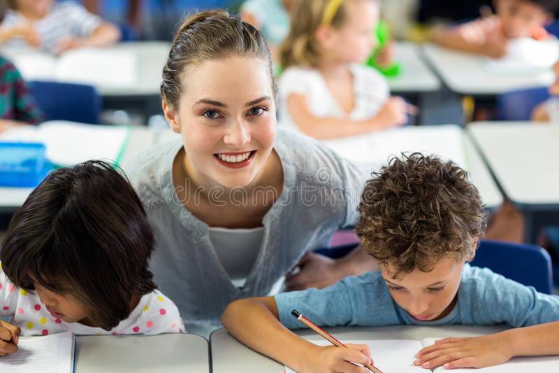 Portrait des écoliers de aide heureux de professeur féminin images libres de droits