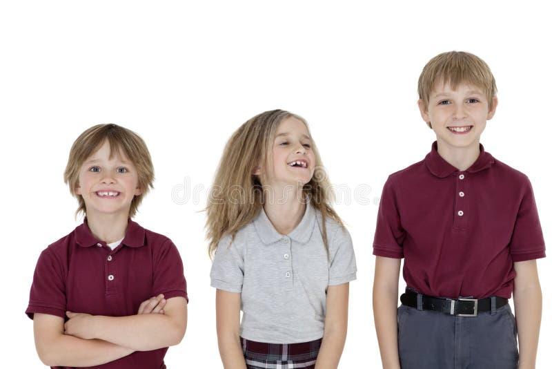 Portrait des écoliers gais dans l'uniforme au-dessus du fond blanc image stock