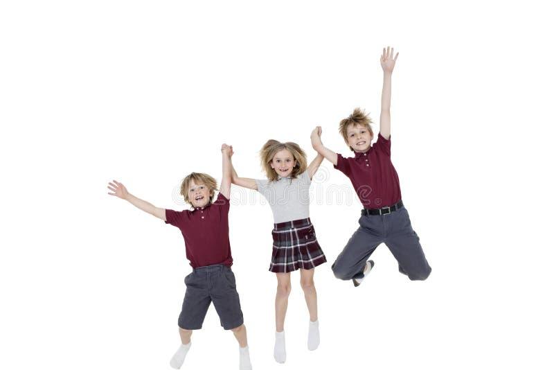 Portrait des écoliers heureux tenant des mains tout en sautant par-dessus le fond blanc photo libre de droits