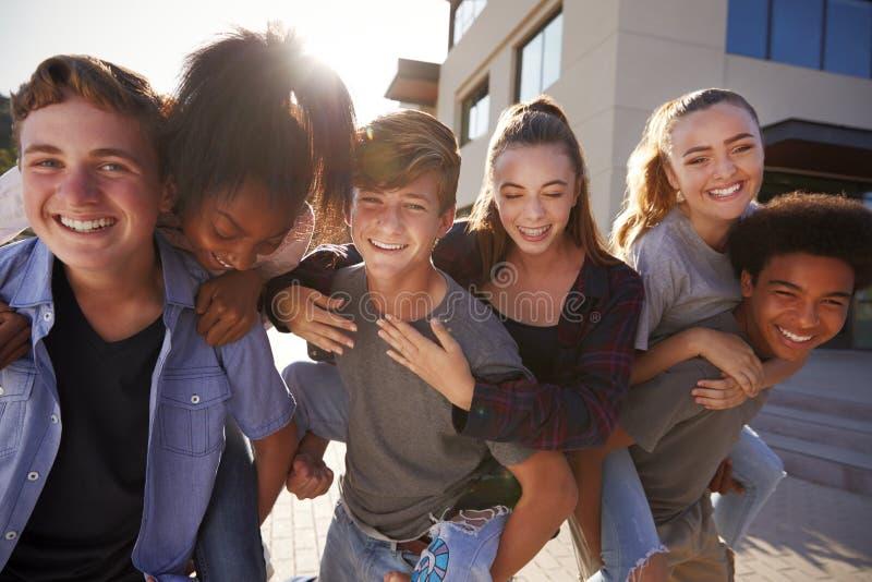 Portrait des étudiants de lycée se donnant des bâtiments d'université de ferroutages image libre de droits