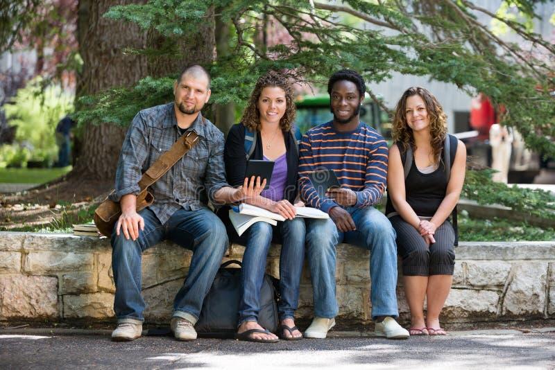 Portrait des étudiants s'asseyant sur le campus photo libre de droits