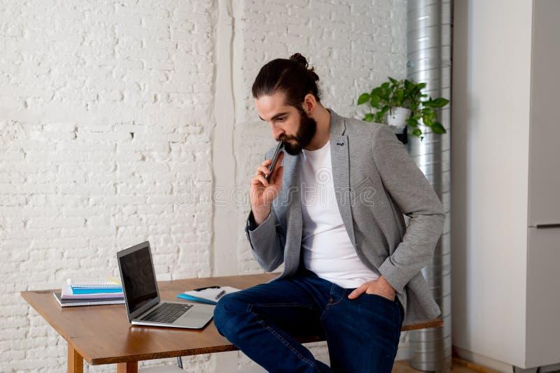 Portrait des affaires parlantes de jeune homme attirant heureux d'entrepreneur sur le mobile photographie stock libre de droits