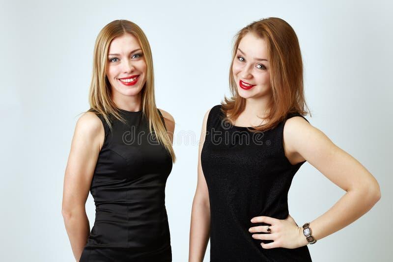 Portrait des amies heureuses posant dans le studio image stock