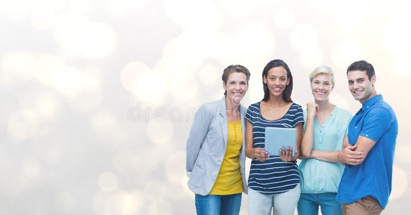 Portrait des amis heureux avec le comprimé numérique contre le bokeh image stock