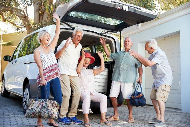 Portrait des amis supérieurs enthousiastes chargeant le bagage dans le tronc de la voiture environ pour partir pour des vacances photo stock