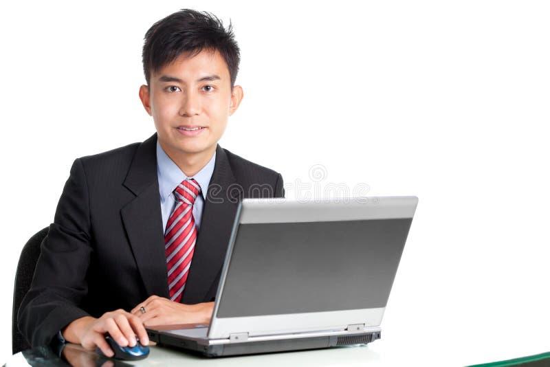Portrait des asiatischen Geschäftsmannes mit Laptop am Schreibtisch lizenzfreies stockbild