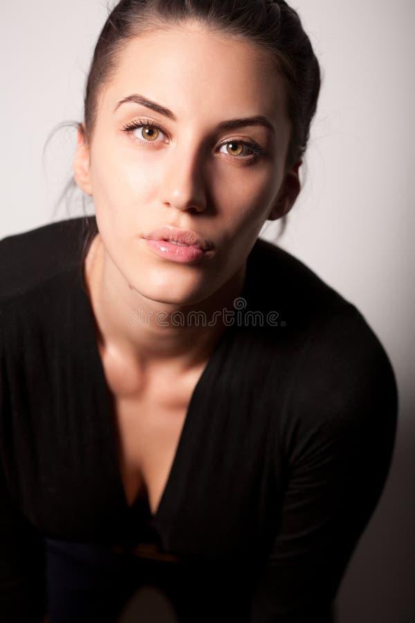 Portrait des attraktiven Brunettemädchens über Grau stockfoto