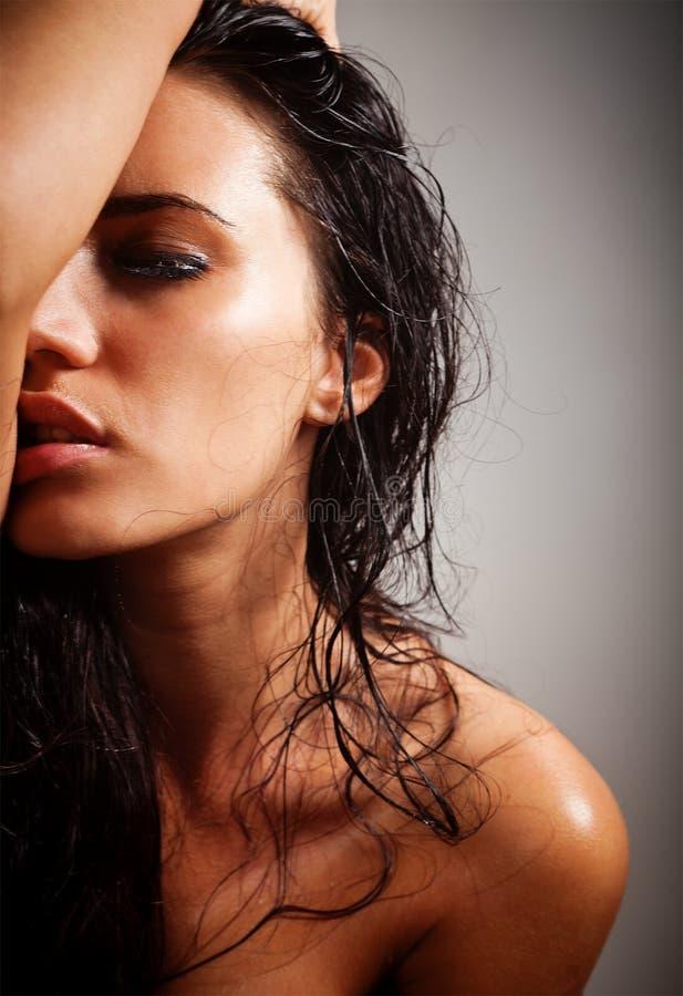 Portrait des attraktiven Brunettemädchens über Grau lizenzfreie stockbilder