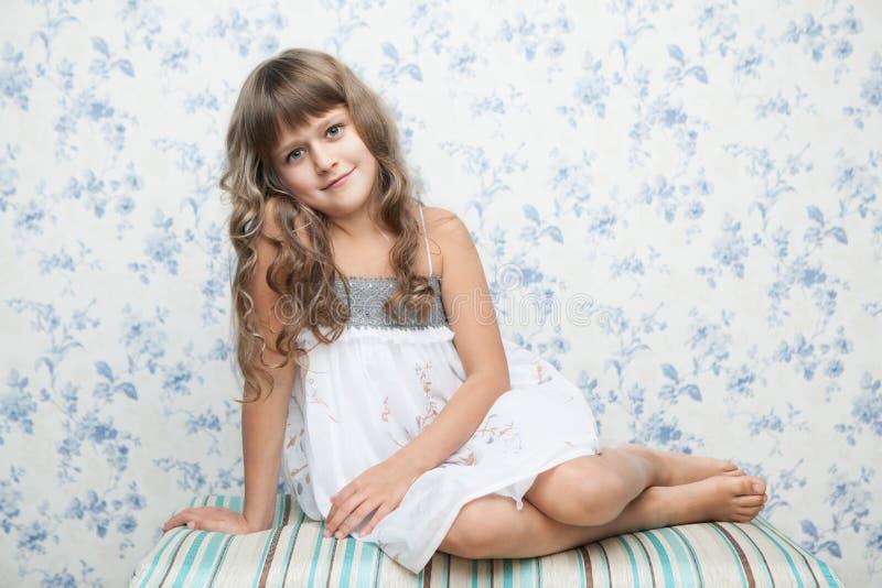 Portrait des aufrichtigen Mädchens in der Sitzenlage lizenzfreie stockfotografie