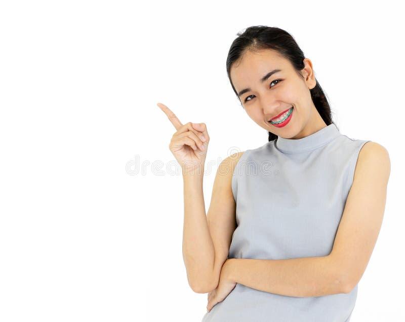 Portrait des bagues dentaires de port de fille asiatique souriant heureusement PO photo stock