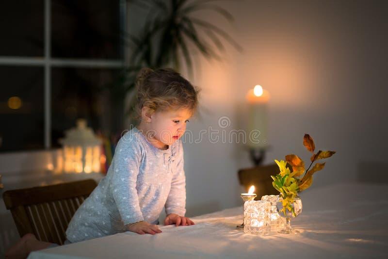 Portrait des bougies de observation de petite fille dans la chambre noire images stock
