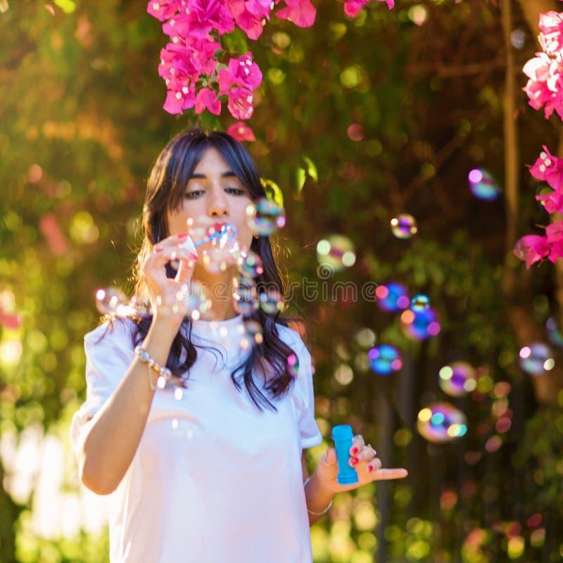 Portrait des bulles de savon de soufflement de jeune femme sur le fond rose de fleurs sur la plage photo libre de droits