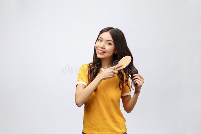 Portrait des cheveux merveilleux de beau peigne de jeune femme d'isolement sur le fond blanc, beauté asiatique image stock