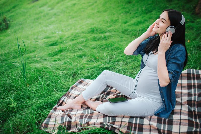 Portrait des cheveux noirs heureux et d'une femme enceinte fière dans une ville à l'arrière-plan Elle s'assied sur un banc de vil photo libre de droits