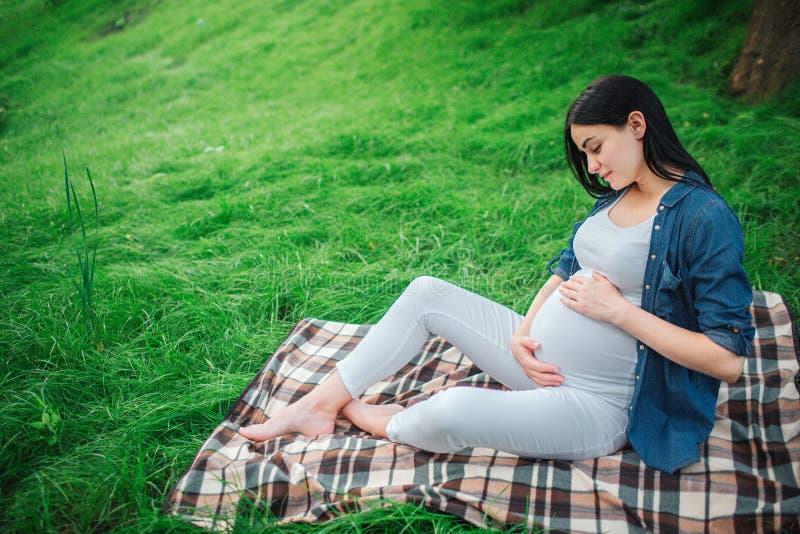 Portrait des cheveux noirs heureux et d'une femme enceinte fière dans une ville en parc Photo de modèle femelle touchant son vent photos stock