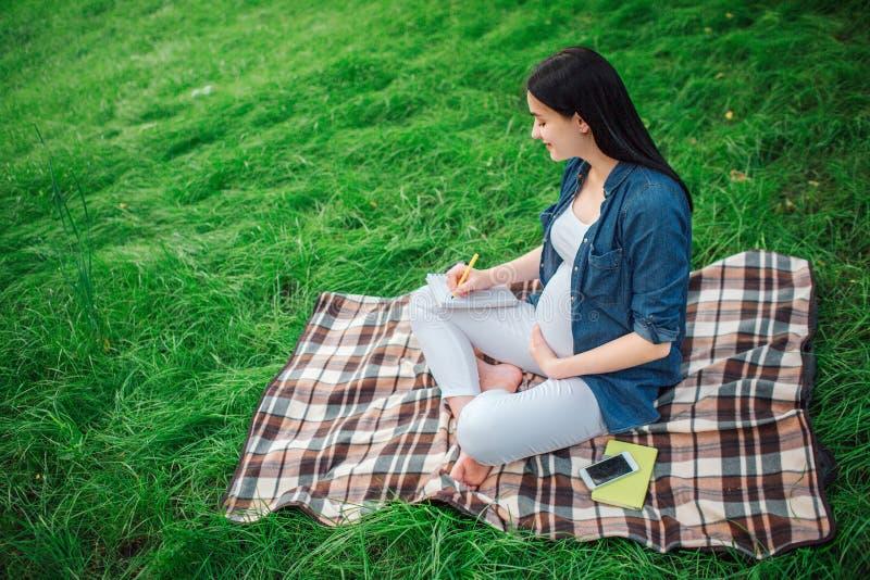 Portrait des cheveux noirs heureux et d'une femme enceinte fière en parc Le modèle femelle se repose sur l'herbe et écrit photographie stock libre de droits