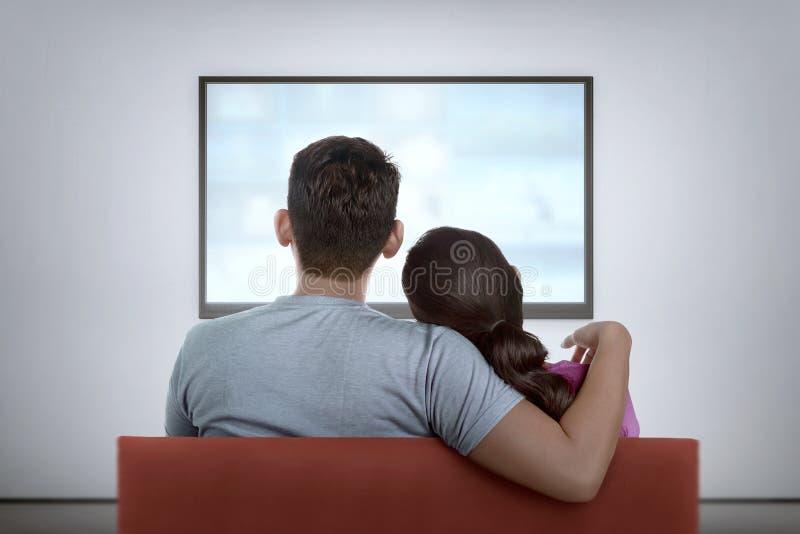 Portrait des couples asiatiques sur le divan regardant la télévision photographie stock libre de droits