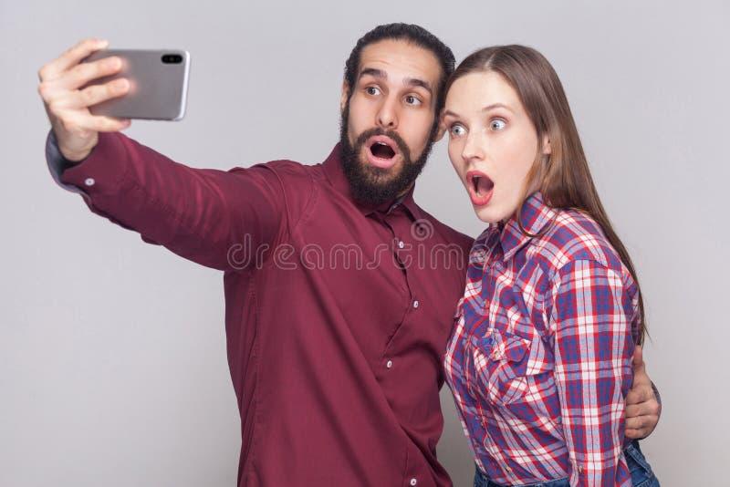 Portrait des couples choqués regardant l'affichage futé mobile de téléphone ils ont lu quelques nouvelles et le regard avec de gr image stock