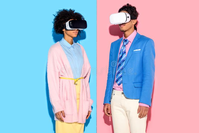 portrait des couples d'afro-américain dans des casques de vr contre le rose et le bleu photo libre de droits