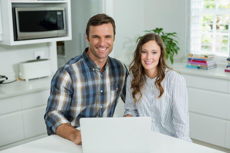 Portrait des couples de sourire utilisant l'ordinateur portable dans le salon à la maison image libre de droits