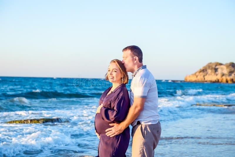 Portrait des couples enceintes d'amour heureux s'embrassant et l'observant en avant à la mer pendant la promenade sur la plage Dé images stock
