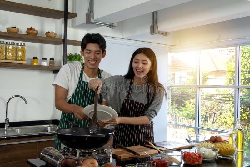 Portrait des couples heureux mignons dans le tablier dans l'action de selfie reparing faisant cuire le petit déjeuner décoré de l photos libres de droits
