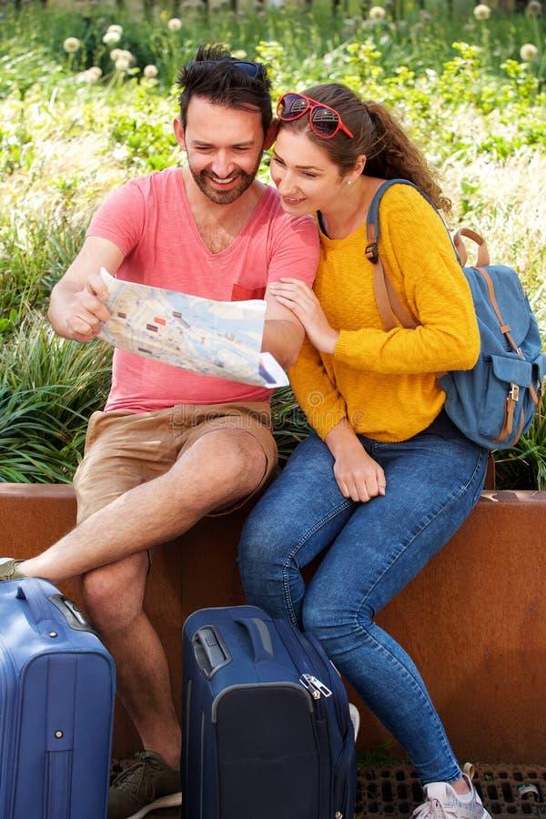 Portrait des couples heureux se reposant ensemble regardant la carte de touristes avec le bagage photo libre de droits