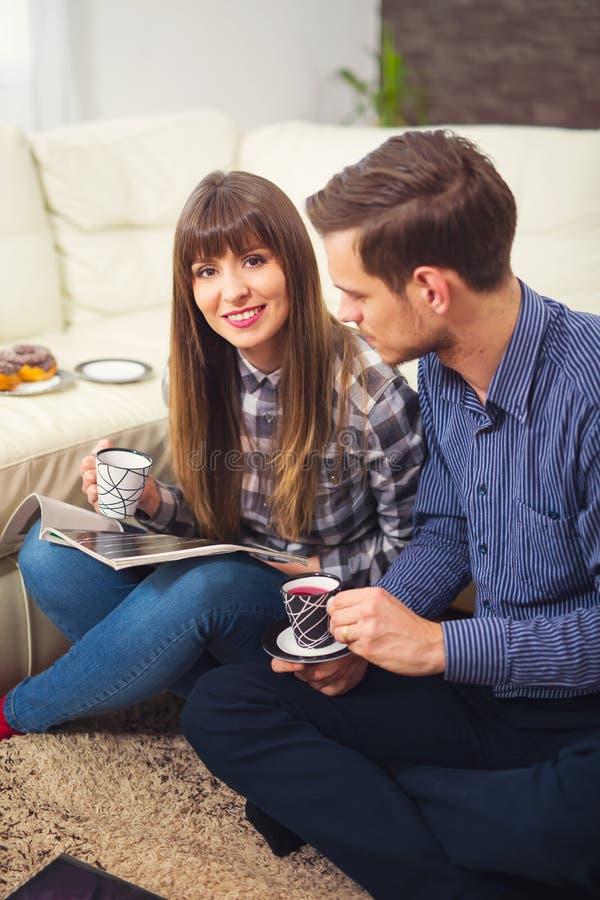 Portrait des couples heureux se reposant sur le divan et lisant un magazine images libres de droits