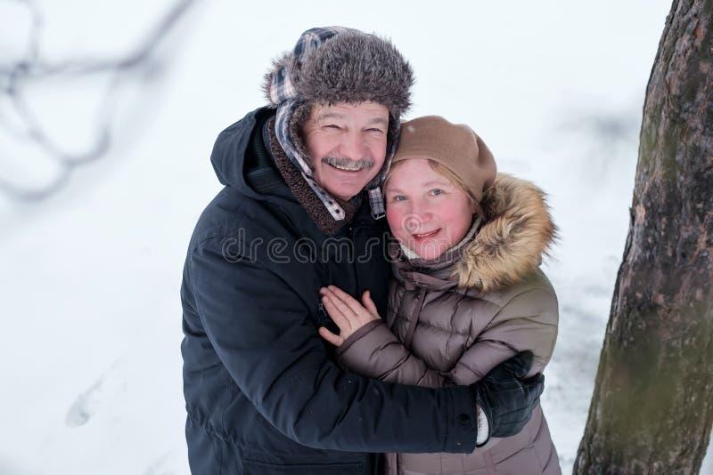 Portrait des couples pluss âgé ayant l'amusement dehors dans la forêt d'hiver photos stock