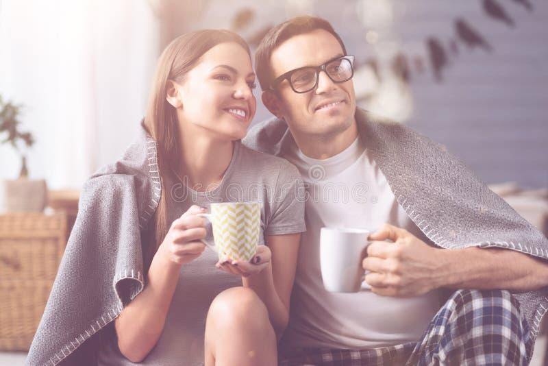 Portrait des couples positifs tout en buvant du thé photos stock