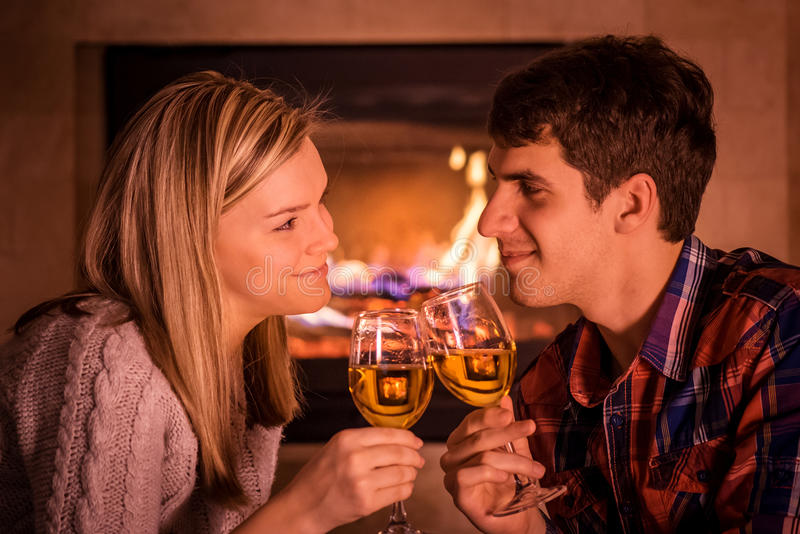 Portrait des couples se reposant près de la cheminée et du vin potable image libre de droits
